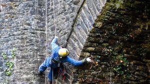 En man hänger från ett rep och arbetar med att ta loss växter från ett slottsvalv på Dunans castle.