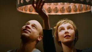 mies ja nainen katsovat lamppuun ylhäällä, toinen kurottaa siihen kädellään