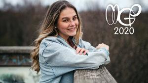 Mirella lutar mot ett staket och ler mot kameran