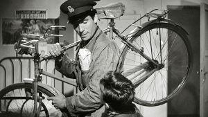 Virkapukuinen mies kantaa polkupyörää olallaan, vierellään pieni poika. Kuva elokuvasta Polkupyörävaras
