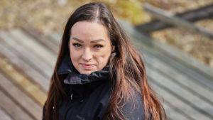 Janina Peräsalo katsoo kameraan kasvoillaan vieno hymy.
