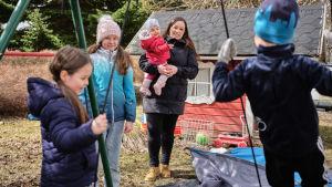 Janina Peräsalo neljän lapsensa kanssa talon pihassa. Yksi lapsista keinuu. Taustalla punainen leikkimökki.