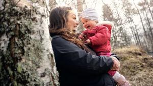 Janina Peräsalo sylissään kuopus Ariela 11 kuukautta. Molemmat nauravat. Ympärillä koivuja ja havumetsää.
