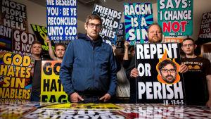 Louis Theroux seisoo mielenosoituskylttien keskellä.