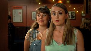 Kaksi nuorta naista (näyttelijät Mathilda Kruse ja Vivi Lindberg) ravintolassa.