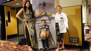 Taiteilija Jenni-Juulia Wallinheimo-Heimonen poseeraa kameralle intialaiskollegansa ja pikkupojan kanssa World Film Festivaaleilla.