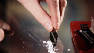 Valkoista jauhetta tasoitellaan metallipalalla