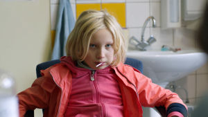 9-vuotias Benni (Helena Zengel) katsoo uhmakkaasti tikkukaramelli suussaan elokuvassa Systeeminmurskaaja (Systemsprenger).