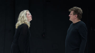 Katariina Kaitueen näyttelemä nainen ja Timo Torikan näyttelemä mies seisovat vastatusten, mustassa tilassa, mustissa vaatteissa, ja riitelevät.