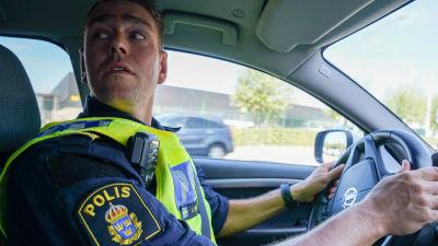 Polisinspektör Jonas Berg tittar över axeln då han kör bil.