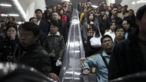 Morgonpendlare på en metrostation i Shanghai.