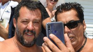 Inrikesminister Matteo Salvini tar en selfie med en anhängare på en strand i Taormina, Sicilien. Båda har bar överkropp.