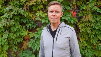 Roy Nielsen står framför växter på en vägg och tittar in i kameran.
