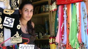 Kaunis basaarikauppias Bybloksessa myy koristeellisia huiveja.