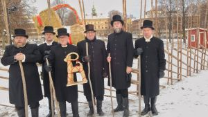Sex svartklädda herrar i cylinderhattar står framför den jättelika Gävlebocken i Gävle.