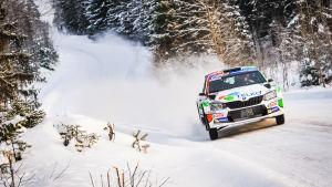 En rallybil susar fram på en snötäckt skogsväg.