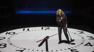 Henna Hakkaraisen näyttelemä toimittaja Tintti juuttuu jättimäisen kellotaulun uumeniin.