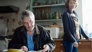 Mies istuu pöydän ääressä ja lukee jotakin, nainen seisoo takana ikkunan edessä ja katsoo mieheen.
