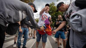 Motdemonstranter bränner Pride-flagga på pridepard i Bialystok, Polen.