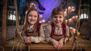 Salasaaren seikkailijat - kaksi lasta hymyilee ohjelman lavasteissa.