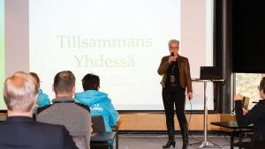 """En kvinna med kort ljust hår talar inför publik. I bakgrunden en skärm där det står """"Tillsammans""""."""