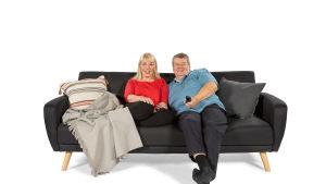 Raija ja Jukka löhöilevät sohvalla.