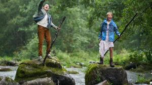 Ramin och Jigi står på varsin sten i en porlande bäck och skriker högt.