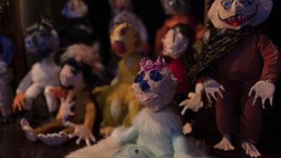 Massor av färggranna små dockor utställda på ett museum.