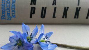 Etualalla sininen kukka ja takana Matti Pulkkisen kirja.