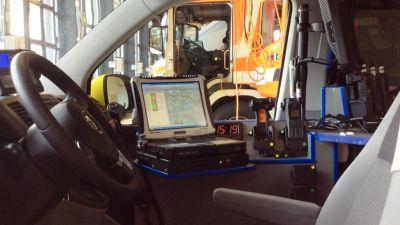 Förarsätet och teknisk utrustning i en fältchefsbil som leder ambulansarbetet. En brandbil syns i bakgrunden.