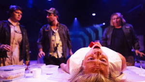Alien tunkee ulos leikkaspöydällä makaavan miehen (Olli Riipinen) rinnasta. Muu miehistö kauhistuneena pöydän ympärillä.