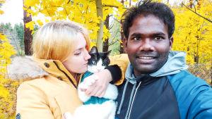 En kvinna med en katt i famnen poserar tillsammans med en leende man. Bakom dem syns gula höstlöv.