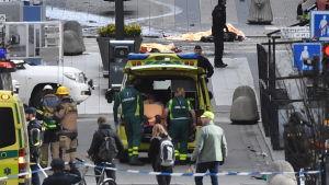 Ambulanser och räddningspersonal i stocholm, efter en terrorattack i centrum av staden.
