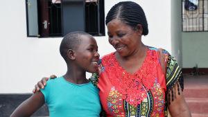 Nuori tyttö ja nainen seisovat vierekkäin, pitävät toisistaan kiinni ja hymyilevät toisilleen.