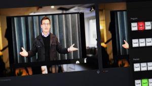 Bild av en skärm där Ulf Kristersson står och håller tal och slår ut med händerna.