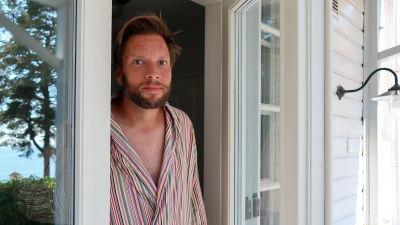 Porträtt av Tuomas Routto som står i dörröppningen till sitt hus i Hangö.