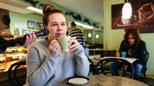 Katja Küttner istuu kahvilassa vakana kahvikuppi kädessään. Mikrofoni äänittää kahvin juomisen ääniä.