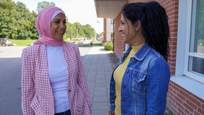 Iman Abbas och Nisreen Kafa skrattar och tittar på varandra.