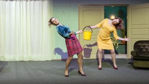 Kaksi naista tanssii näyttämöllä, keltaiset ämpärit käsissään. Rooleissa Aleksinja Lommi ja Elina Knihtilä.