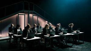 Joukko näyttelijöitä istuu pimeällä näyttämöllä. Kaikilla on tumma puku ja aurinkolasit, he tuijottavat pöydällään olevaa läppäriä.