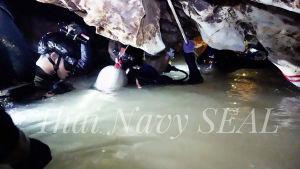 Några räddningsdykare tar sig fram genom en trång gång.
