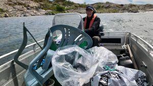 En äldre man, Folke Österman kör sin båt. I båten finns stora mängder plastavfall. Bland annat plastpåsar och trasiga trädgårdsstolar.