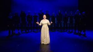 En kvinna i vit klänning sjunger på en scen. Bakom henne står en grupp svartklädda gestalter i en halvcirkel.