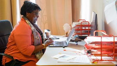 Honorette Muhanzi tittar på sin dator och ler.