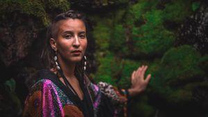 Magdalena katsoo suoraan kameraan keskellä metsää.