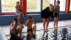 En siminstruktör visar några pojkar simrörelser vid en simbassäng