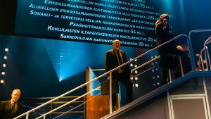 Liukuportaat nousevat näyttämöllä, portaissa seisoo hahmoja tummissa puvuissa (Timo Tuominen, Jukka-Pekka Palo ja Katariina Kaitue). Taustakankaalla lista Sipilän hallituksen tekemistä leikkauksista.