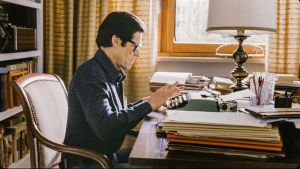 Mies istuu työhuoneessa työpöydän äärellä.