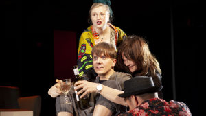 Ryhmä taiteilijoita istuu toisiinsa kietoutuneina ja juo viiniä. Rooleissa Laura Rämä, Eero Ritala, Lotta Kaihua ja Tommi Korpela.