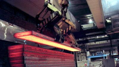Glödande längder av färskgjuten stål staplas på rad i ett stålverk.